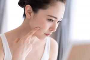 鏡の前で肌を確認する女性