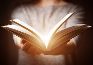 光る本を持つ女性